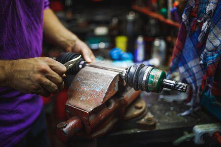 ATV constant-velocity CV joint repair by hands in old garage 版權商用圖片