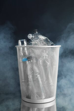 trash can with wasted plastic bottles, black background with smoke, pollution concept