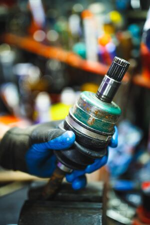 hand holding ATV constant-velocity CV joint, repair in old garage