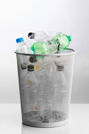 trash can with wasted plastic bottles, grey background