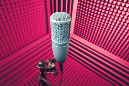 professional microphone in sound recording studio, purple acoustic foam background
