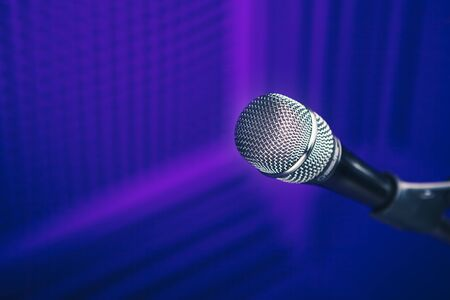microphone on stand, purple background with acoustic foam wall in studio Reklamní fotografie