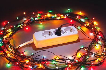 Christmas garland lights circle around electric extension cord