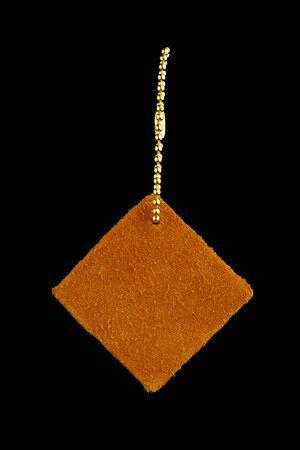 leather shape sample tag on small chain, isolated on black