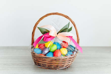 Easter color eggs in festive gift basket, light gray wooden background