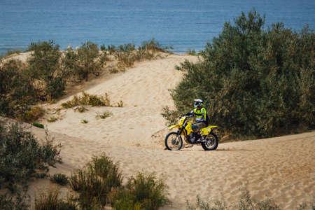 off-road motorcycle enduro motocross rider on sand dune, blue sea background