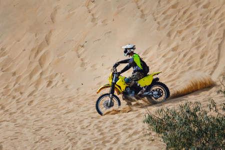 off-road motorcycle enduro motocross rider on sand dune Фото со стока