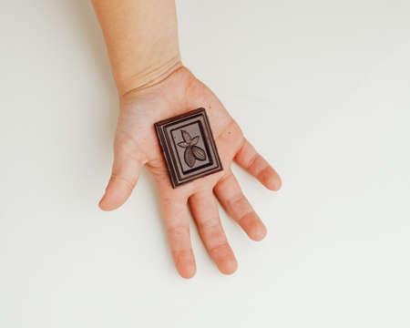 child holding a piece of dark chocolate bar in hand