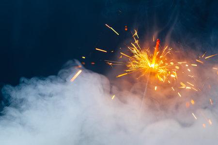 fire sparkler in dense smoke, abstract Christmas firework background 免版税图像
