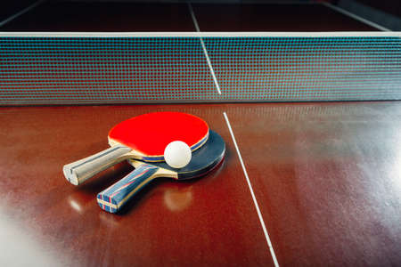 table tennis rackets and ball, net background