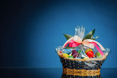 Easter gift basket with multicolor eggs, blue background