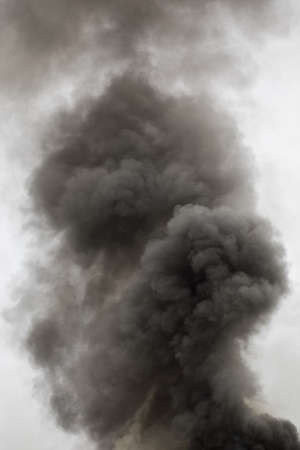 black smoke trail of burning house