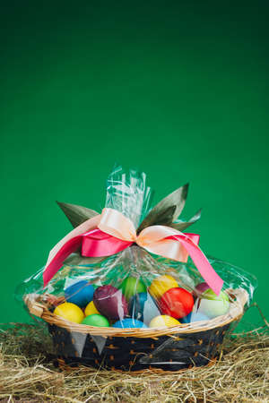 Easter gift basket with multicolor eggs, green background Banque d'images