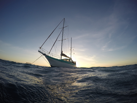 Ankered down Sailing Vessel Watermusic with the sunset in the back. Cairns, Queensland, Australia.