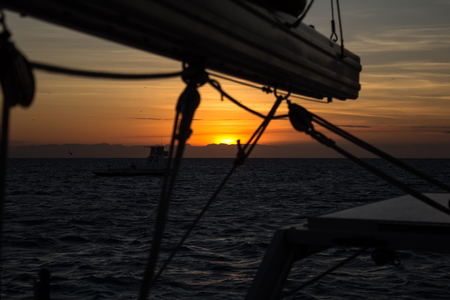 whitsundays: The sun sets into the coast. View from a sailing boat anchored at Lizard Iceland, Queensland, Australia