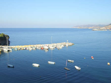 Pier with boats in small greek fishing village on Crete island