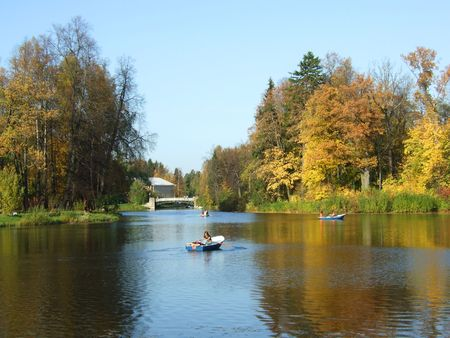 A pond in a park. Autumn. People on rented boats.