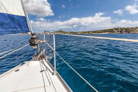 water's edge: Nose boat with a sail and an anchor on a background of the coast on a sunny day. Mallorca, Spain Stock Photo
