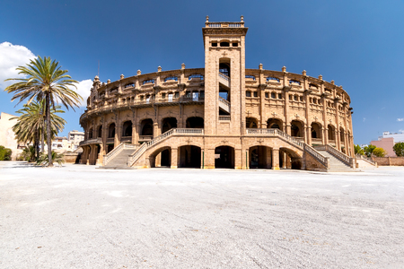 bullfighting: Panorama building for bullfighting in Mallorca on a sunny day. Old bullring on the area with palm trees. Quiet sunny day. On blue sky clouds float. Editorial