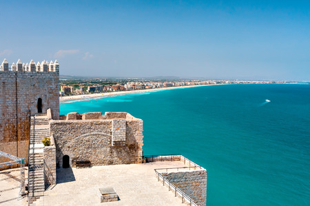 beaches of spain: View of the beach at Valencia and the castle of Peniscola, Spain. Beautiful coastline with beaches, hotels and turquoise sea. Part of the old fortress. Clear sunny day, cloudless sky.