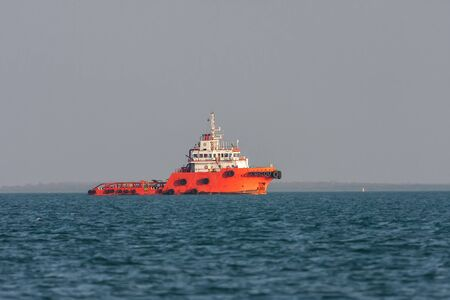 superstructure: Orange rescue ship sails across the bay at sunset. Bright orange hull and white superstructure. The blue sea and ashore in a gray haze. Sun at sunset vividly illuminates the ship. Stock Photo