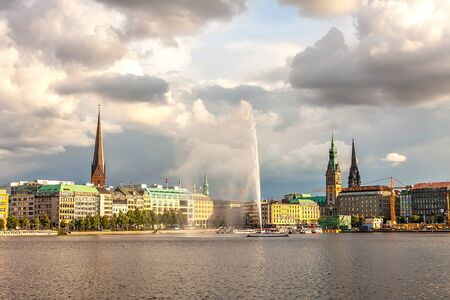 passenger ships: Panorama Hamburg city center with the Town Hall and a fountain. Alster lake with a fountain in the background the town hall and the cathedral at sunset. Passenger ships are at berth. Dark clouds in the sky illuminated by the sun. Stock Photo