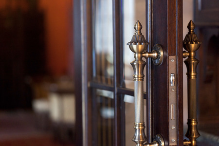 glass door: Metal door handle on a wooden door. Open wooden door with metal handle. Stock Photo