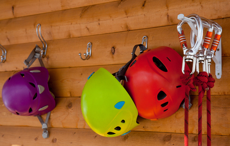 Helmets and harnesses carabiners hanging on the wooden wall.