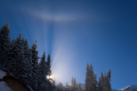 fine particles: The sun illuminates a cloud of fine ice particles. Winter rainbow in the mountains. Stock Photo