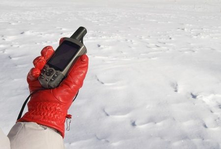 red glove with a GPS navigator on a background of white snow Stock Photo