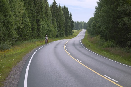 lone cyclist riding along the edge of the winding road in the forest