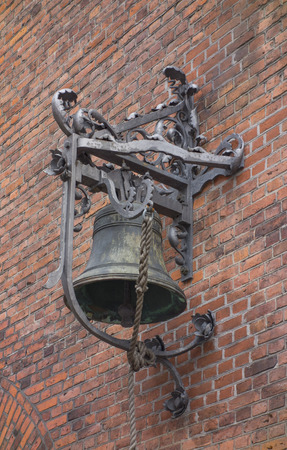 Alarm bell hanging on a brick wall