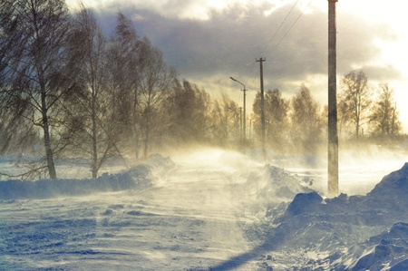 sweeps: The strong wind sweeps snow on the winter road