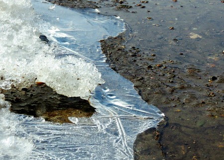 rifts:     Springtime first blue thawed patches appear on puddle                            Stock Photo