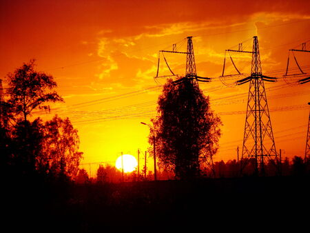 over voltage: The evening sun sets over high voltage support