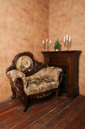 Old fashioned interior with luxury armchair, fireplace, candelabras and small Christmas tree on ocher wallpaper background photo