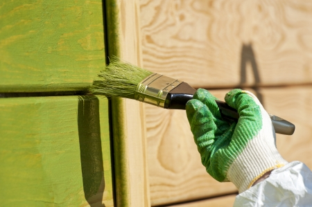 peintre en b�timent: main avec un mur en bois de peinture de pinceau en plein air abattu vert Banque d'images