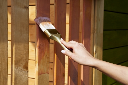 woman s hand with a paint brush painting wooden terrace in pink outdoor shot Stock Photo - 23099663