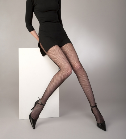 lycra: shapely girls legs with black fishnet tights, fashion shoes and cocktail dress on gray background studio shot Stock Photo