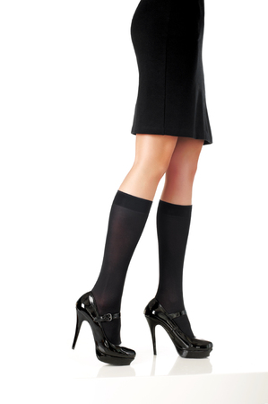 elegant woman model legs with black skirt, fashion shoes and half-hose on white background