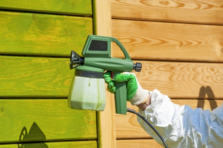 paint gun: Hand painting wooden wall with spray gun in green