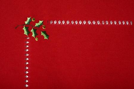 Christmas red cloth fragment embroidered with holly macro shot holiday background  photo