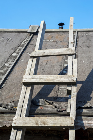 roofing felt: old wooden staircase to roof and into sky Stock Photo