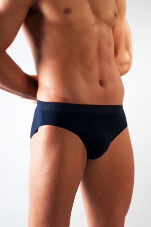 pantalones cortos: atractiva fragmento de cuerpo masculino con ropa interior de color azul sobre fondo blanco Foto de archivo
