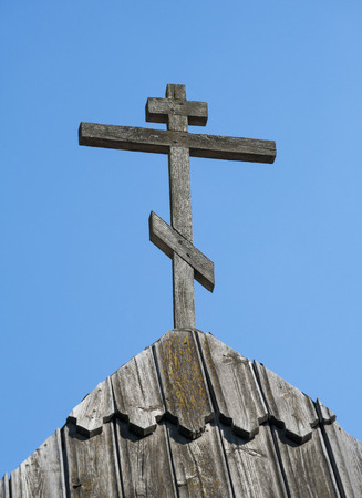 old wooden cross on roof against blue sky background Stock Photo