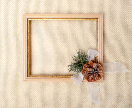 frame with branch of Christmas tree, pinecone and white bow on beige plaid background  photo