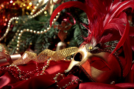 magic Christmas background with carnival golden mask on  red silk  fabric photo