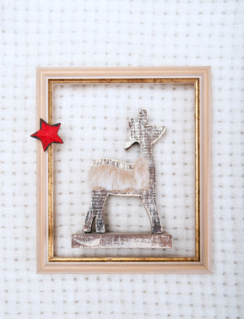 Christmas reindeer framed picture with fur and red star on white wool plaid background photo