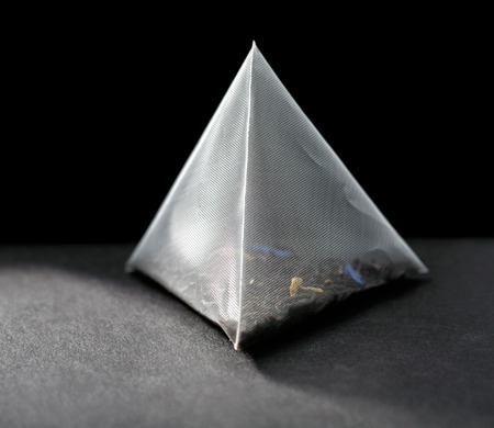tea bag: pyramid tea bag on black background Stock Photo