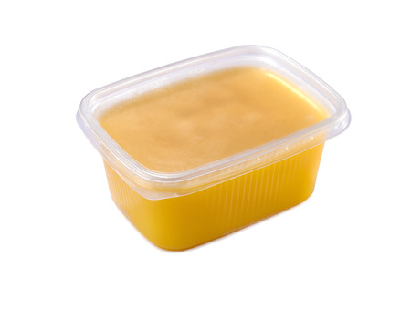 clarified: plastic container with ghee butter isolated on white background Stock Photo